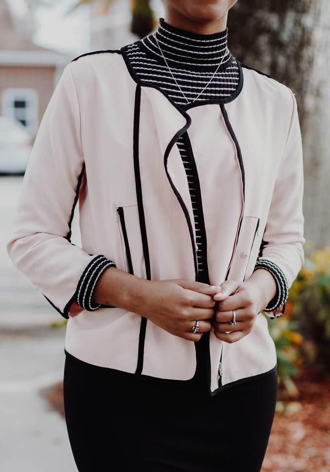 Femme portant jupe noire moulante avec un sous-pull noir rayures blanches horizontale et veste blanche bordure noire