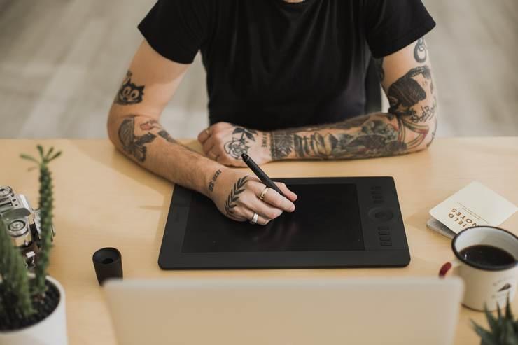 Homme tatoué travaillant dans les arts graphiques