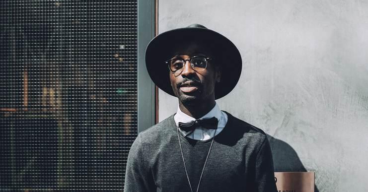 Homme noir très stylé portant le chapeau, une chemise blanche avec un noeud papillon. recouvert d'un pull gris