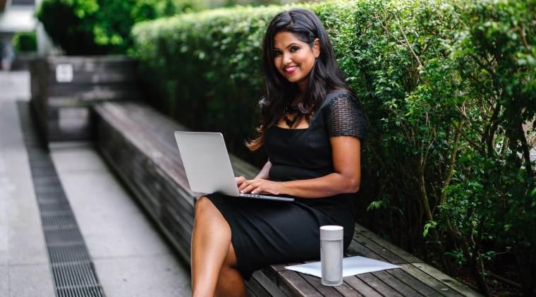 Femme d'origine hindu travaillant dehors sur son ordinateur. Elle porte une robe noire chic.