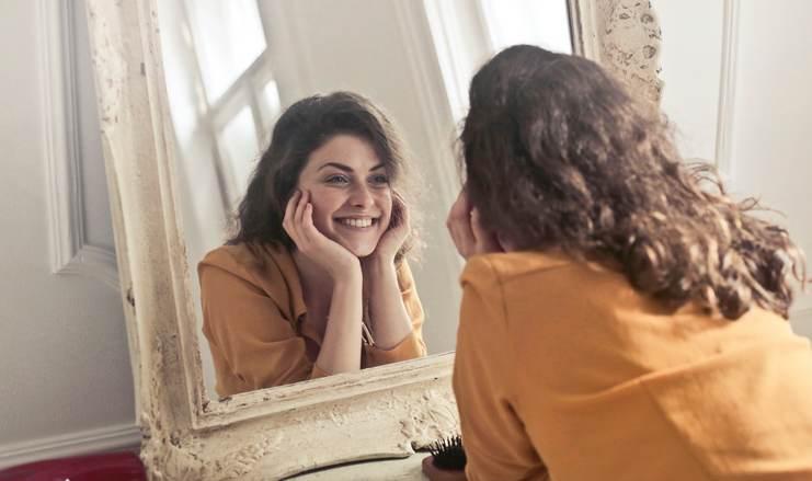 Jeune femme, brune aux cheveux longs ondulés, se regardant dans une glace, souriante
