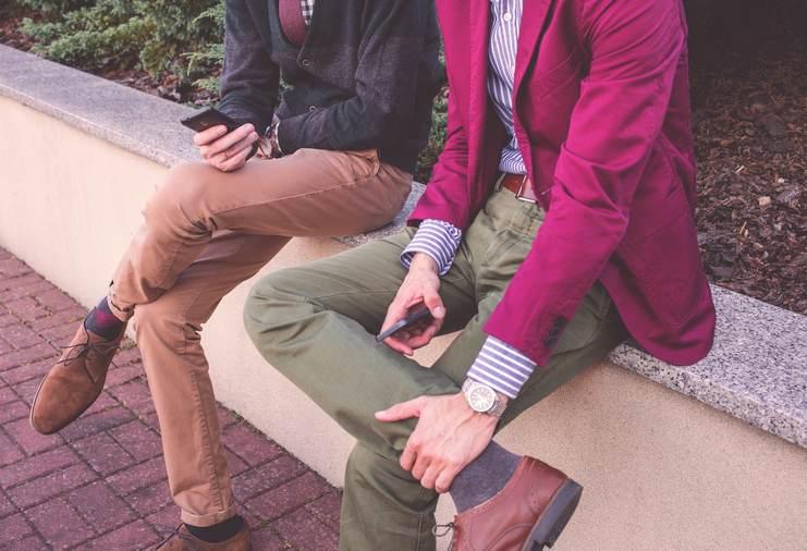 Deux collègues hommes discutant et portant des costumes colorés