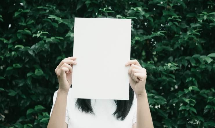 femme brune aux cheveux longs qui se cache le visage avec une feuille blanche