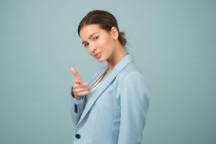 Jeune femme coiffée d'un chignon et portant une veste bleu ciel