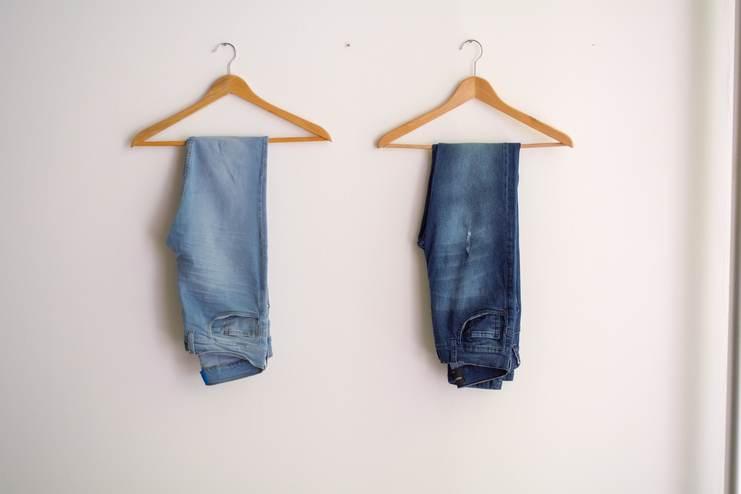 2 jeans (bleu clair et bleu foncé) accrochés à un contre en bois, côte à côte