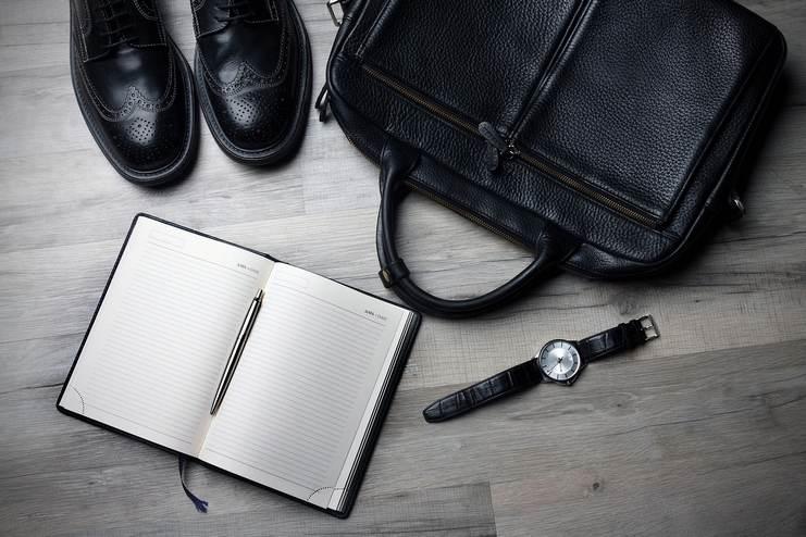 Gros plan sur les accessoires d'un homme d'affaires : chaussures cirées, montre, carnet, beau stylo et sacoche en cuir