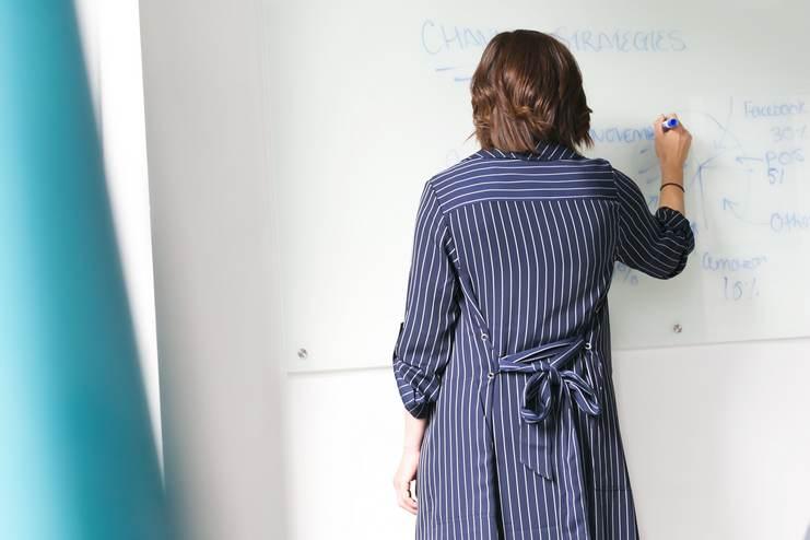 Femme portant une longue robé rayée écrivant sur un tableau blanc