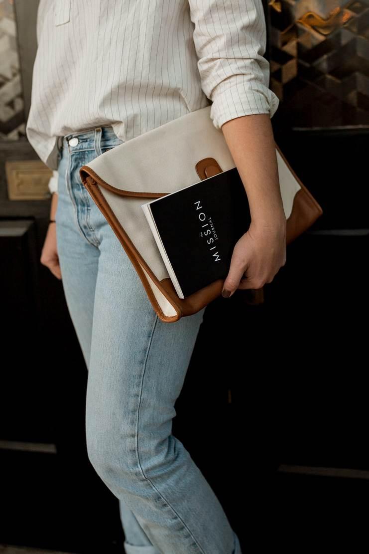 Femme portant un jean et une chemise à rayure et une belle sacoche