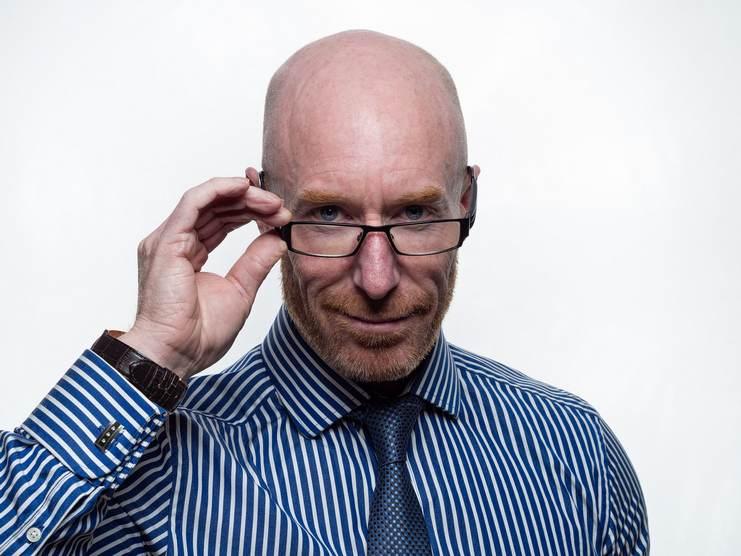 Homme chauve portant une barbe rousse bien taillé, des lunettes et une chemise rayée et cravate bleue