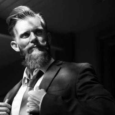 Portrait noir et blanc d'un homme barbu, style hypster, habillé en costume cravate