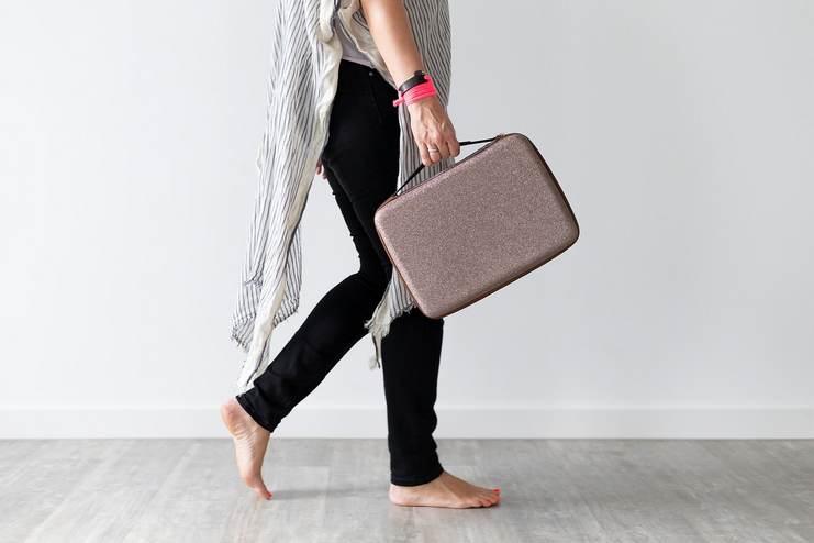 Femme qui se prépare pour aller travailler. Elle porte une longue tunique, un jean noir et est pied nus.