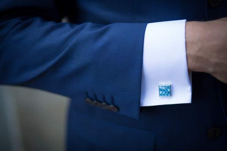 Homme portant un costume bleu et en zoom un bouton de manchette assorti