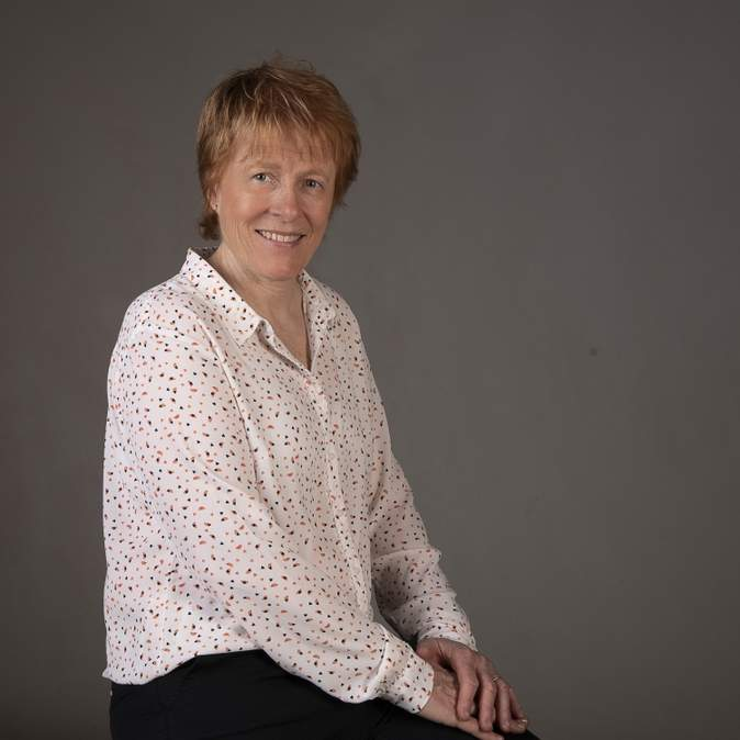 Nathalie lors de sa séance photo au Studio Mir, habillée en pantalon tailleur et chemise blanche à pois colorés